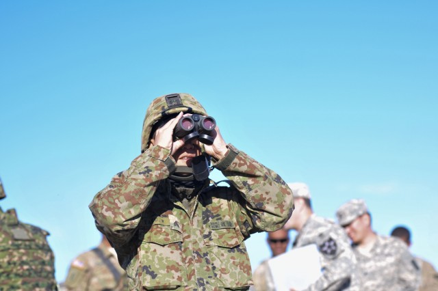 A soldier assigned to the 33rd Infantry Regiment, 10th Division, Japanese Ground Self-Defense Force observes a range through a set binoculars before conducting a mounted operation live fire exercise during Rising Thunder 2015 at Yakima training Center, Wash., Sept. 9. Rising Thunder 2015 is the 22nd annual bilateral exercise between the U.S. Army's I Corps elements and the JGSDF. (U.S. Army photo by Sgt. Eliverto V. Larios)