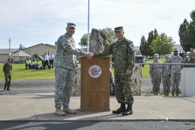Lt. Col. Dan Rayca, commander of the 4th Battalion, 23rd Infantry Regiment, 2nd Stryker Brigade, 2nd Infantry Division, left and Col. Shoji Shimomoto, commander of the 33rd Infantry Regiment, 10th Division, Japanese Ground Self-Defense Force, shake hands to mark the beginning of Rising Thunder 2015 during an opening ceremony at the Yakima Training Center in Yakima, Wash., Sept. 8, 2015. Rising Thunder 2015 is the 22nd annual bilateral exercise between the U.S. Army's I Corps elements and the JGSDF. (U.S. Army photo by Sgt. Eliverto V. Larios)