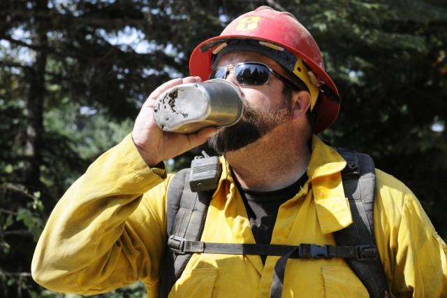 Chris Scott, a military crew adviser tasked to provide oversight of Soldiers assigned to Task Force First Round, drinks water in between overseeing the Soldiers, out of Joint Base Lewis-McChord, Wash., conduct fire suppression in hopes of slowing the fire burning through Colville National Forest, Wash., Aug. 25, 2015. The Soldiers arrived last Saturday and have been conducting training or suppressing fires more than 10 hours a day.