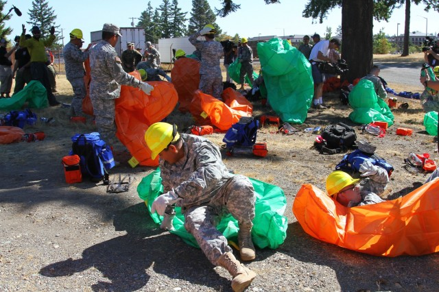 "Soldiers with 5th Battalion (HIMARS), 3rd Field Artillery Regiment, 17th Field Artillery Brigade, 7th Infantry Division, practice utilizing their fire protection shelters on Joint Base Lewis-McChord with the assistance of their trainers prior to their upcoming firefighting mission, Aug. 19, 2015. ""Our battalion received orders and is prepared to mobilize approximately 200 Soldiers in support of the National Interagency Fire Center's efforts,"" said Lt. Col. James Dunwoody, commander of the 5-3FA. ""Soldiers are being trained by a team of professional wildland fire agency personnel."""