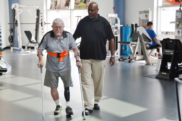 Physical therapy technician Troy Hopkins assists retired Maj. Gen. William L. Moore Jr. at the Center for the Intrepid in Brooke Army Medical Center's outpatient rehabilitation facility, Sept. 3, 2015. Moore served as Brooke Army Medical Center's commander from 1988-1991.