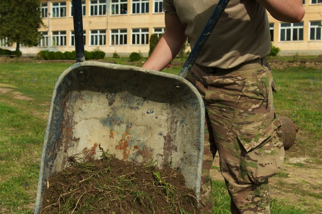 U.S. Army Pfc. Connor McKinney, a paratrooper assigned to 1st Battalion, 503rd Infantry Regiment, 173rd Airborne Brigade, out of Vicenza, Italy, dumps weeds collected from around the Mokren Elementary School as part of a community outreach event held in Mokren, Bulgaria,  Sept. 7, 2015.