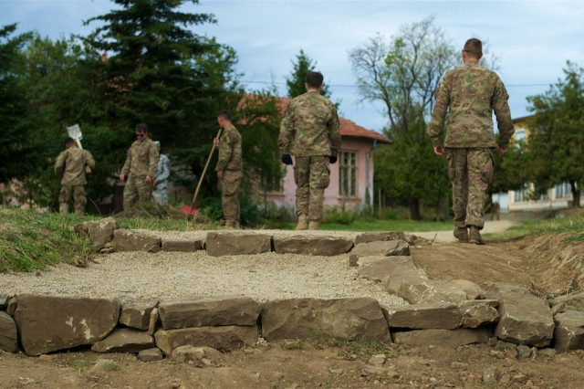 Soldiers, assigned to the Bulgarian Civil-Military Cooperation Team, and the U.S. Army's 173rd Airborne Brigade, out of Vicenza, Italy, and the 85th Civil Affairs Brigade, out of Fort Bliss, Texas, work to clear a new pathway to Mokren Elementary School as part of a community outreach event held in Mokren, Bulgaria, Sept. 7, 2015.