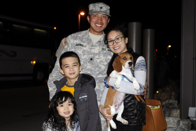Spc. Kenneth Aquinde, a Soldier assigned to Task Force First Round poses with his wife, Andrea; son, Ezekiel, 8, and daughter, Bella, 3, after arriving back to Joint Base Lewis-McChord, Wash., Sept. 13, 2015. Aquinde, along with an additional 250 plus Soldiers, recently returned from supporting wildfire suppression operations in which the task force helped contain approximately 79 percent of a wildfire that grew to over 25,000 acres in Northeastern Washington.
