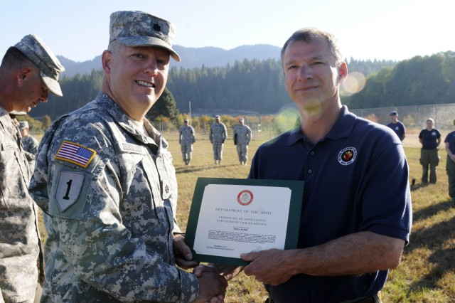 Lt. Col. James Dunwoody, left, commander, Task Force First Round, out of Joint Base Lewis-McChord, Wash., and Rod Blooms, military liaison officer, National Interagency Fire Center, pose for a photo during a recognition ceremony at the Kalispel Indian Reservation, Wash., Sept. 13, 2015. Dunwoody presented Bloom, and his fellow military advisors, certificates of appreciation for their support to the task force while it conducted fire suppression operations throughout Northeastern Washington for the past three weeks.