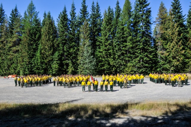 Solders and military crew advisors assigned to Task Force First Round, out of Joint Base Lewis-McChord, Wash., stand in formation prior to conducting a team building event in the Colville National Forest, Wash., Sept. 12, 2015.  After conducting wildfire suppression operations for three weeks, the Soldiers and their civilian counter parts concluded the mission with a team building event that tested physical abilities and mental knowledge gained throughout the operation.