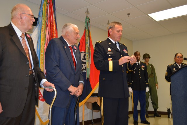 Brig. Gen. Steven Ainsworth, commander 94th Training Division, explains the significance of his commander's coin before presenting it to WWII veteran Vincenzo Geramita during a ceremony where Ainsworth awarded Bronze Star medals to Geramita and Andrew Cella at Fort Dix, N.J., Sept. 12, 2015. Ainsworth, who also presented a coin to Cella, noted that this was the first time he'd been afforded the opportunity to present the coin to WWII veterans.