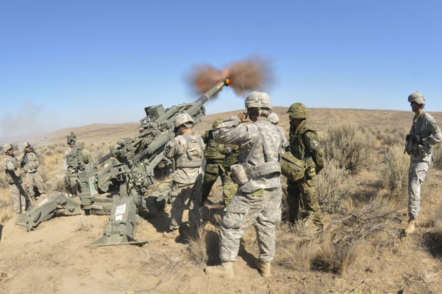 Artillerymen with the 33rd Infantry Regiment, 10th Division, Japan Ground Self-Defense Force, look on as Soldiers from Battery C, 1st Battalion, 37th Field Artillery Regiment, 2nd Division Artillery fire an M777 howitzer while conducting a live fire training exercise during Rising Thunder 2015 at Yakima Training Center, Wash. Sept. 10, 2015. Rising Thunder 2015 is the 22nd annual bilateral exercise between the U.S. Army's I Corps elements and the JGSDF. (U.S. Army photo by Sgt. Eliverto V. Larios)