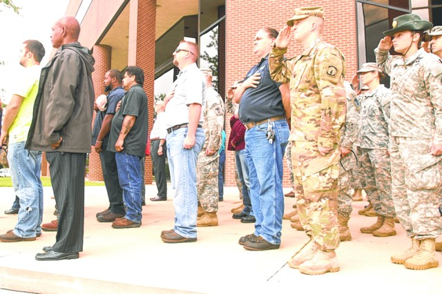 "Community members render honors during the playing of ""Taps,"" ending a Patriot Day remembrance ceremony on the steps of Hoge Hall at the Maneuver Support Center of Excellence Plaza Sept. 11."