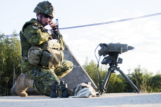 Capt. Dave Smith from the Royal Canadian Regiment of Infantry, designates a target and radios to the AH-64 Apache pilots as part of the training operation Ample Strike 2015 in Boletice, Czech Republic, September 16, 2015.  Operation Ample Strike is a multi-national training operation with an emphasis on land-air integration with 18 different nations.  The 12th CAB contributed four AH-64 Apaches to the exercise.  (U.S. Army photo by Spc. Nicholas Redding)