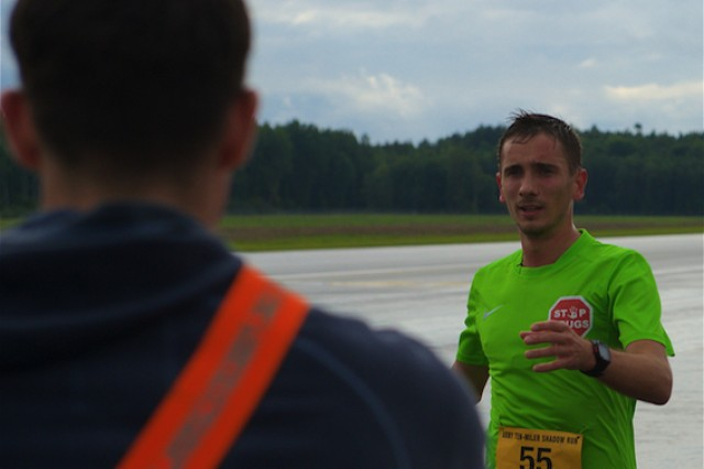 Latvian Airmen Artjoms Rekunenko grabs water at the final check point during the 10-Mile Shadow Run held on Lielvarde Airfield, Latvia, Sept. 18. The run, which mirrors the Army Ten-Miler being held Oct. 9-10 in Washington, was conducted to increase camaraderie among U.S. and Latvian forces participating in Operation Atlantic Resolve, an ongoing, multinational partnership focused on combined-training and security cooperation between the U.S. and other NATO allies. (Photo by U.S. Army Staff Sgt. Brooks Fletcher, 16th Mobile Public Affairs Detachment)