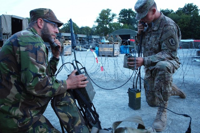 Dutch army Sgt. 1st Class Jan Klerx, left, and U.S. Army Spc. Adams conduct secure radio interoperability validation using a tactical voice bridge radio as part of Exercise Strong Engineer in Marche-en-Famenne, Belgium, Sept. 10, 2015.