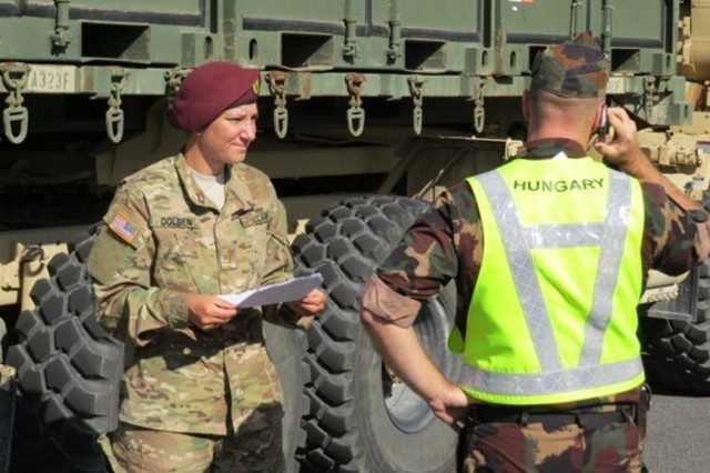 Second Lt. Amanda Dolsen, a platoon leader with 173rd Airborne Brigade Support Battalion, speaks with a Hungarian army official during a convoy from Italy to Ukraine, in support of Operation Fearless Guardian, Sept. 9.