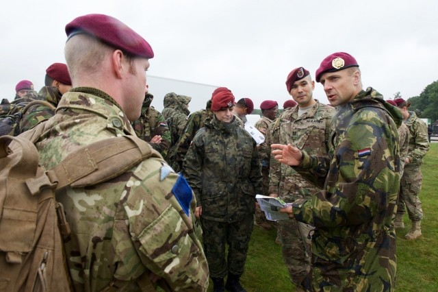 A paratrooper from the Dutch 11th Air Mobility Brigade explains the march route to paratroopers from the U.S., United Kingdom and Poland Sept. 17, 2015, near Arnhem, Netherlands. The commemoration brought together approximately 1000 allied paratroopers from the U.S., Belgium, Germany, Italy, the Netherlands, Poland and the U.K. for several days of combined airborne operations and ceremonies. Market Garden was the largest airborne operation in history, taking place from Sept. 17-25, 1944. The march led paratroopers a total of 17 kilometers from the Ginkel Memorial to the Frost Bridge, both key locations during the exercise. (U.S. Army photo by Sgt. Daniel Cole, U.S. Army Europe Public Affairs)