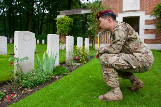 U.S. Army 1st Lt. Jeffrey Kim, a paratrooper with the 173rd Airborne Brigade, stops at the grave of a British paratrooper at Oosterbeek cemetery Sept. 17, during a commemorative road march to pay tribute to those who jumped here as part of Operation Market Garden 71 years ago. The commemoration brought together approximately 1,000 allied paratroopers from the U.S., Belgium, Germany, Italy, the Netherlands, Poland and the U.K. for several days of combined airborne operations and ceremonies. Market Garden was the largest airborne operation in history, taking place from Sept. 17-25, 1944. The march led paratroopers a total of 17 kilometers from the Ginkel Memorial to the Frost Bridge, both key locations during the exercise. (U.S. Army photo by Sgt. Daniel Cole, U.S. Army Europe Public Affairs)