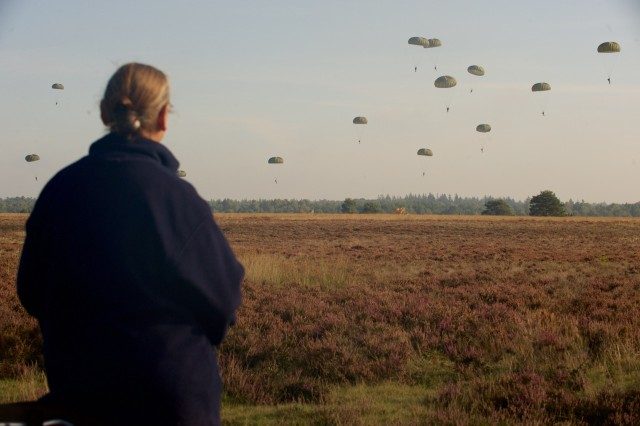 HOUTDORPERVELD DROP ZONE, the Netherlands - A Dutch citizen watches paratroopers from the U.S., U.S., Belgium, Germany, Italy, the Netherlands, Poland and the U.K conduct an airborne operation Sept. 18, at Houtdorperveld Drop Zone, the Netherlands as part of a commemoration of the 71st anniversary of Operation Market Garden. The commemoration brought together approximately 1,000 allied paratroopers from the seven NATO allies for several days of combined airborne operations and ceremonies. Market Garden was the largest airborne operation in history, taking place from Sept. 17-25, 1944.