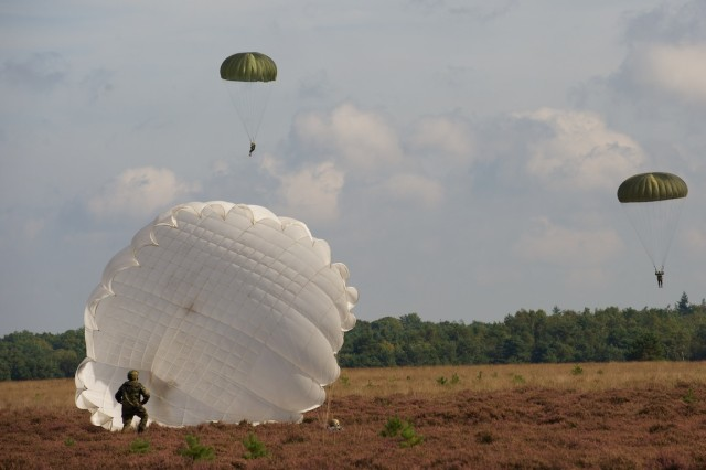 HOUTDORPERVELD DROP ZONE, the Netherlands - A German paratrooper (kneeling) from the Luftlandebrigade 1 gathers begins his parachute after landing on Houtdorperveld Drop Zone, the Netherlands, Sept. 18, 2015, as part of the 71st anniversary of Operation Market Garden. The commemorative multinational jump included troops from the U.S., Belgium, Germany, Italy, the Netherlands, Poland and the U.K and was part of a series of airborne operations and ceremonies to commemorate the anniversary. Market Garden was the largest airborne operation in history, taking place from Sept. 17-25, 1944.