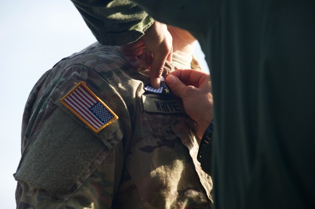 HOUTDORPERVELD DROP ZONE, the Netherlands - A U.S. Army paratrooper receives his Dutch parachute badge from a Dutch Army jumpmaster Sept. 18, 2015, after jumping onto Houtdorperveld Drop Zone, the Netherlands as part of the 71st anniversary of Operation Market Garden. The commemorative multinational jump included troops from the U.S., Belgium, Germany, Italy, the Netherlands, Poland and the U.K and was part of a series of airborne operations and ceremonies to mark the event. Market Garden was the largest airborne operation in history, taking place from Sept. 17-25, 1944.