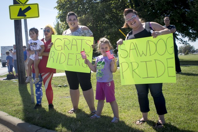 Fort Campbell community members hold signs and cheer on the riders on the last leg of the 167-mile bike ride.
