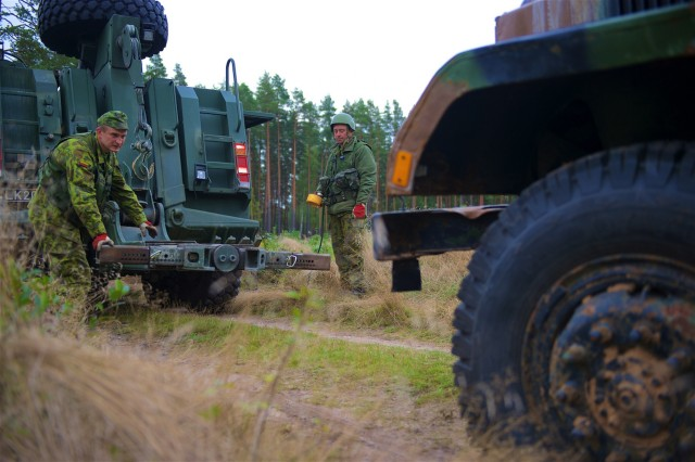 Lithuanian Armed Forces Cpl. Edvardas Jaskelevicius, a logistician assigned to the Lithuanian Main Support Battalion, Logistic Support Command, guides a tow receiving to a disabled vehicle as apart logistic operations as part of Baltic Push in Atari, Latvia, Sept. 23. Baltic Push provided an opportunity for U.S. and Lithuanian logistic units to work together to sustain NATO forces across international borders and is part of Operation Atlantic Resolve, an ongoing, multinational partnership focused on combined-training and security cooperation between the U.S. and other NATO allies. (Photo by U.S. Army Staff Sgt. Brooks Fletcher, 16th Mobile Public Affairs Detachment)