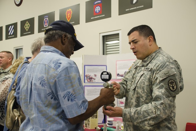 Staff Sgt. Osuna Castro, Occupational Therapy, Blanchfield Army Community Hospital, tests Fillmore Kelley's grip strength during the Retiree Appreciation Day, Sept. 19, 2015.