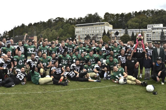 Troopers from the 2nd Cavalry Regiment football team celebrated their 35-0 victory alongside their on-field rivals, the Prague Black Panthers, after their football game in Cesky Krumlov, Czech Republic, Sept. 26, 2015. The team participated in an American football game with the local Czech Republic semi-professional football team as the unit helped to commemorate the 70th anniversary of Cesky Krumlov's liberation during World War II while also demonstrating the U.S. commitment to their NATO and Czech allies. (U.S. Army photo by Sgt. William A. Tanner/released)