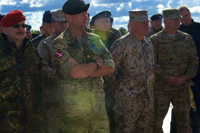 From left, Staff to the Office of International Cooperation, Lt. Col. Allert Bernd; Danish army 1st Brigade commander, Brig. Gen. Per Knudsen; Latvia chief of defense, Lt. Gen. Raimonds Graube; and 4th Infantry Division deputy commanding general, Brig. Gen. Timothy Daugherty, listen to a concept of operation brief during the Silver Arrow 2015 DV Day held in Adazi, Latvia, Sept. 27, 2015. Silver Arrow is a Latvian-led cooperative training exercise with Denmark, Canada, Germany, the U.S. and the UK. There are more that 1,000 participant and the exercise is designed to improve cooperation among NATO member states.