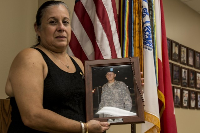 """Griselda Guerra, mother of Pvt. Gary Guerra, 27, who died in a car accident in 2008, holds up a picture of her son at the Gold Star Mother's Day event at Fort Hood Survivors Outreach Services Sept. 26. According to the Army's proclamation, Gold Star Mother's Day was observed Sept. 27 this year """"to remember and honor fallen service members and acknowledge the enormous burden their mothers continue to carry as they mourn the loss of their child."""""""