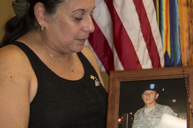 "Griselda Guerra, mother of Pvt. Gary Guerra, 27, who died in a car accident in 2008, holds up a picture of her son at the Gold Star Mother's Day event at Fort Hood Survivors Outreach Services Sept. 26. According to the Army's proclamation, Gold Star Mother's Day was observed Sept. 27 this year ""to remember and honor fallen service members and acknowledge the enormous burden their mothers continue to carry as they mourn the loss of their child."""