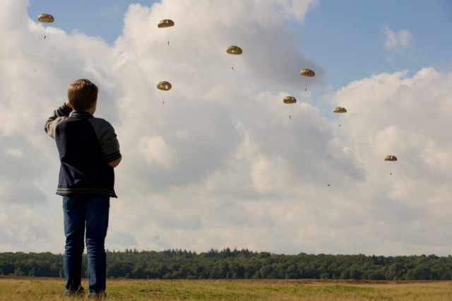 A young Dutch watches paratroopers from the U.S., Belgium, Germany, Italy, the Netherlands, Poland and the U.K jump Sept. 19, as part of a commemorative event held to remember Operation Market Garden. local The event, which marked the 71st anniversary of Operation Market Garden, the largest Airborne jump in history, hosted attendees who outlined more than a kilometer of the drop zone's border. Many surrounded the Airborne Monument in Ginkel Heide, which stands for Market Garden's fallen paratroopers, overlooking the historic drop zone in the town of Ede. The commemoration brought together approximately 1,000 allied paratroopers from the seven NATO allies for several days of combined airborne operations and ceremonies. Market Garden was the largest airborne operation in history, taking place from Sept. 17-25, 1944. (U.S. Army photo by Sgt. Daniel Cole, U.S. Army Europe Public Affairs)