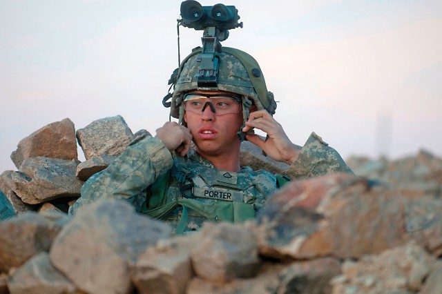 As night begins to fall on the desert, Pfc. Daniel Porter, an all-source analyst for the 2nd Armored Brigade Combat Team (ABCT), 1st Cavalry Division, secures his night vision optics to his Advanced Combat Helmet during a rotation at the National Training Center, Fort Irwin, California, in February. Both the optics and the helmet are products of extensive research in Army labs.