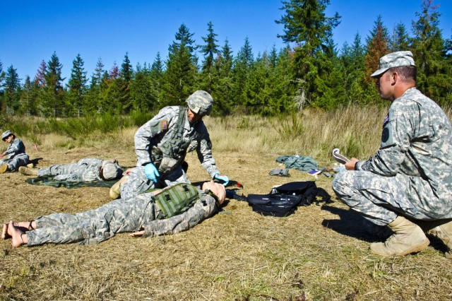 Staff Sgt. Nick Rodriguez, middle, health care specialist, Headquarters and Headquarters Detachment, 47th Command Support Hospital, and an Expert Field Medical Badge candidate puts his lifesaving skills to test, while being graded on combat testing lane one during the 2015 EFMB qualifications week on Joint Base Lewis-McChord, Wash., Sept. 24-29. The EFMB consists of three CTL lanes, day and night land navigation, a written test, and a 12-mile ruck march. (U.S. Army photos by Sgt. Jasmine Higgins, 28th Public Affairs Detachment)