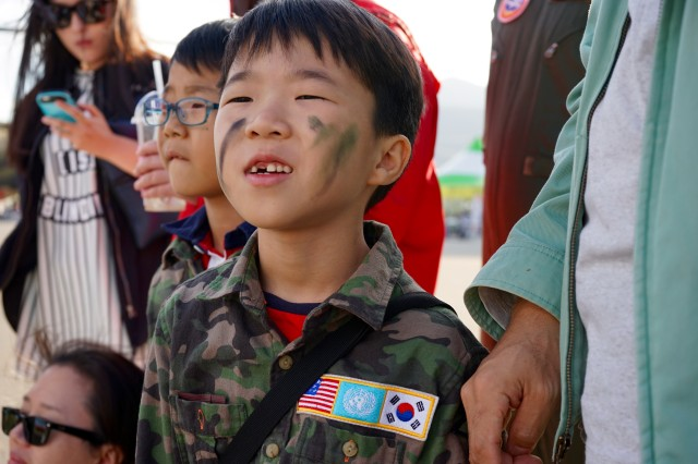 A boy watches as the Eighth Army Band performs in the daily parade in the main thoroughfare at the 2015 Republic of Korea Ground Forces Festival in Gyeryong, South Korea Oct. 2, 2015.