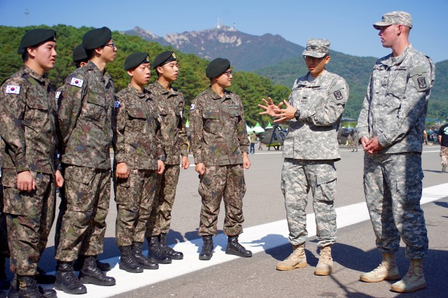 Korean Augment to the U.S. Army Soldier Cpl. Mun, Hak-bong and PV2 Bryan Gilliand, both of 2nd Battalion, 1st Air Defense Artillery Regiment explain what they do to Republic of Korea Army Soldiers during the 2015 Republic of Korea Ground Forces Festival in Gyeryong, South Korea Oct. 5, 2015.