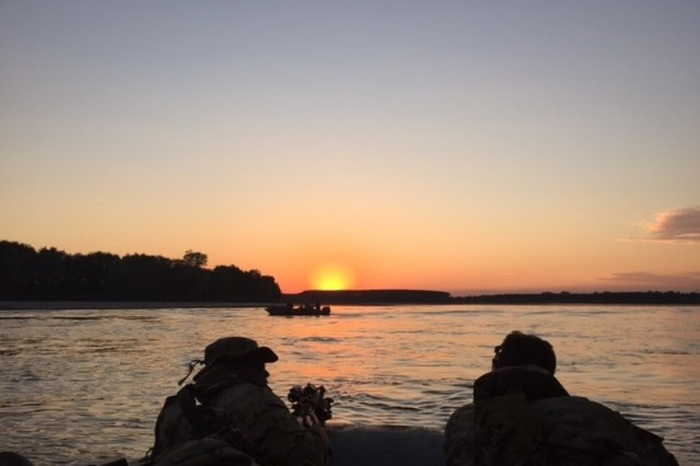 U.S. and Italian paratroopers observe a water crossing during a combined bridgehead seizure in Piacenza, Italy, Oct 2, 2015.