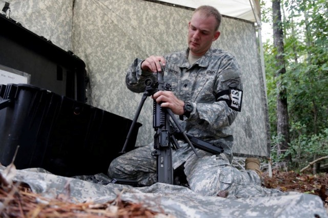 Spc. Travis Shooks, assigned to the 517th Geospatial Engineer Detachment, U.S. Army Africa, assembles a weapon from a box containing parts during the U.S. Army Best Warrior Competition at Fort A.P. Hill, Va., Oct. 5, 2015. The competition is a grueling, weeklong event that tests the skills, knowledge, and professionalism of 26 warriors representing 13 commands. (U.S. Army Photo by Spc. William Lockwood/Released) #BestWarrior
