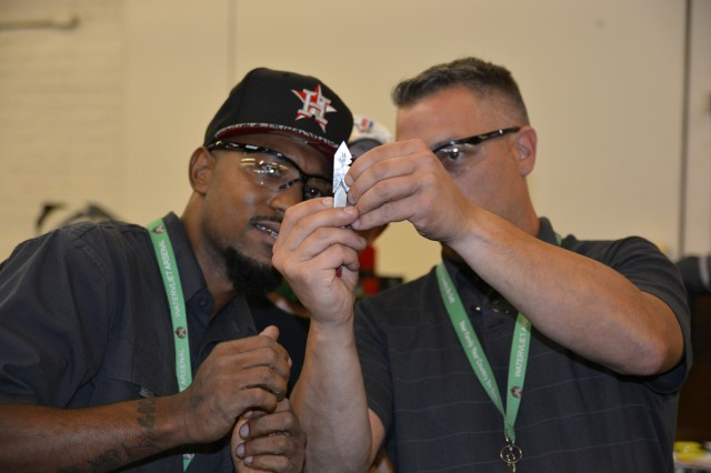 Apprentice Program Supervisor John Zayhowski, right, checks out the first cut made by apprentice Derrell Barefield.