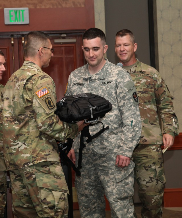Command Sgt. Maj. Jeffery Hartless presents a backpack to 1st Lt. Michael Piscetelli