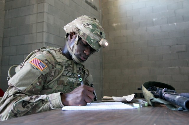 Spc. Emanuel L. Moore, assigned to 1st Battalion, 160th Special Operations Aviation Regiment (Airborne), U.S. Army Special Operations Command, writes a situation report during the U.S. Army's Best Warrior Competition at Fort A.P. Hill, Va., Oct. 6, 2015. The competition is a grueling, weeklong event that tests the skills, knowledge, and professionalism of 26 warriors representing 13 commands. (U.S. Army photo by Pfc. Michael Parnell/Released) #BestWarrior