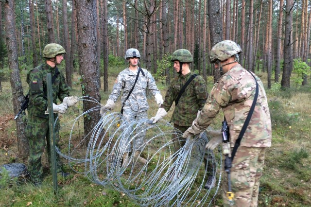 U.S. and Lithuanian combat engineers set up concertina wire as part of a combined Best Sapper Competition, hosted by the 173rd Airborne Brigade in Rukla, Lithuania, Sept. 28, 2015.