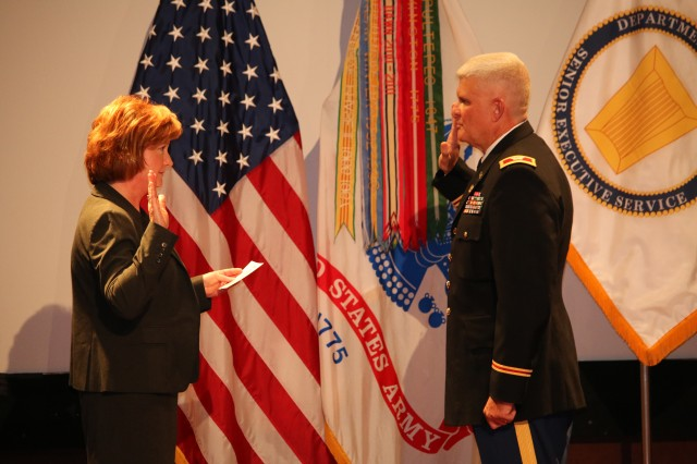 Lisha Adams, executive deputy to the Army Materiel Command's Gen. Dennis Via, conducts the oath of office during the Sept. 29 promotion ceremony for Col. Ray Sartain.