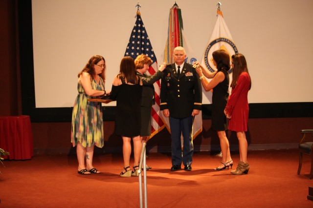 Col. Ray Sartain is surrounded by his family -- including two daughters -- as his wife Kim, at right, and officiant Lisha Adams, executive deputy of the Army Materiel Command, attach his new shoulder straps in place during his promotion ceremony on Sept. 29.