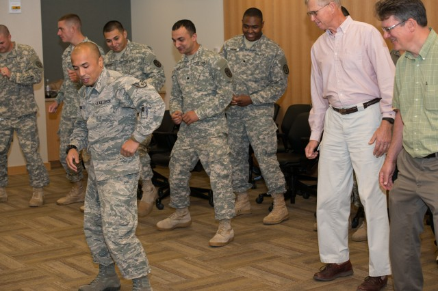 A group of male attendees learn how to perform dance moves from the Hispanic American tradition during a Hispanic American Heritage Month celebration hosted by the U.S. Army Medical Research Institute of Chemical Defense Sept. 23.