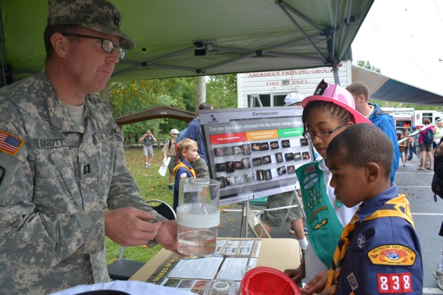 Capt. Brian Knott, an entomologist in the Entomological Sciences Program, explains the contents of a mosquito breeder to local Scouts so they can recognize mosquitoes at home and identify breeding sites. The bottom half contains water and mosquito larvae, and after they emerge, the adults fly up into the top half.