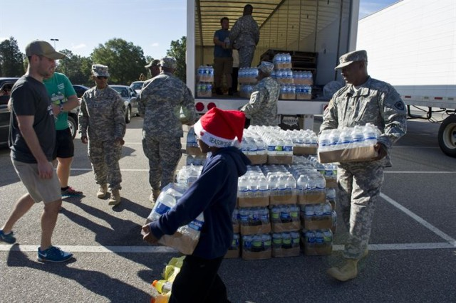 South Carolina Army National Guardsmen, from the 742nd Maintenance Company, law enforcement personnel and volunteers distribute drinking water to residents affected by flooding caused by Hurricane Joaquin in Columbia, S.C., Oct. 6, 2015.