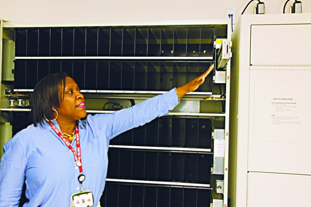 EISENHOWER ARMY MEDICAL CENTER, FORT GORDON, Ga. -- Lizzie Gaither, Eisenhower Army Medical Center's assistant housekeeper, points out part of the control system of the new scrubs vending machine, Oct. 7, 2015. Two scrub vending systems are being installed to help reduce loss and ensure clinical staff has the proper clothing at a moment's notice. (Photo by David M. White/RELEASED)