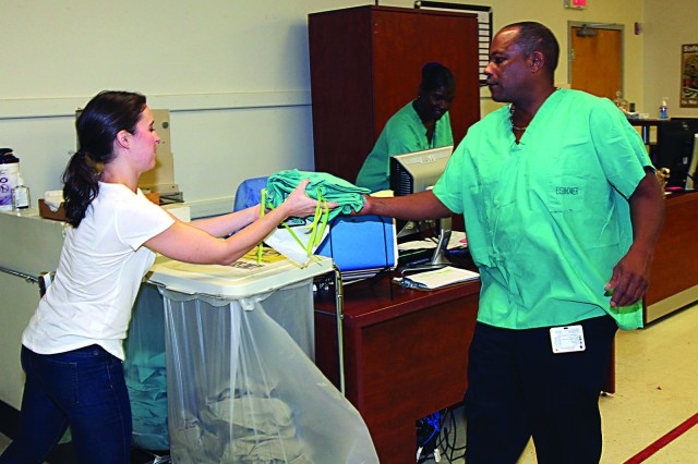 EISENHOWER ARMY MEDICAL CENTER, FORT GORDON, Ga. -- Percy Moore, right, hands a fresh set of scrubs to a member of Eisenhower Army Medical Center's clinical staff as Angela Scott, center, handles the paperwork, Oct. 8, 2015. Moore and Scott are two of three employees of contractor AJ Services who, on a daily basis, pick up and distribute the linens from around the hospital. They also handle receiving clean linen, and at 11 a.m. every weekday, they ship soiled linen to an off-site laundry. (Photo by David M. White/RELEASED)