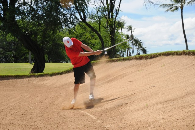 Sgt. 1st Class Marin Perez hits a ball from a sand trap at the Signal Week Golf Scramble at Joint Base Pearl Harbor, Hickam, HI on Sept. 17, 2015.