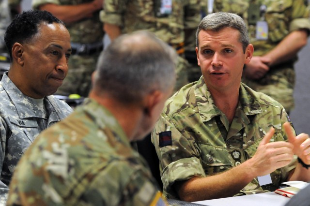 Brigadier Rob Sergeant, commander of the United Kingdom's 12th Armored Infantry Brigade, speaks with Gen. Dennis L. Via, commanding general, U.S. Army Material Command and other distinguished visitors about his unit's mission during Network Integration Evaluation 16.1 at Fort Bliss, Texas, Oct. 1, 2015. The 12th Armored brought its entire headquarters of nearly 200 soldiers to NIE 16.1, as they operate alongside Soldiers of the U.S. 1st Armored Division headquarters for this year's exercise. (Army photo by Sgt. Jessica R. Littlejohn, 24th Press Camp Headquarters)