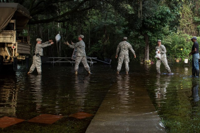 Soldiers, assigned to the South Carolina National Guard, unload sandbags to help prevent further residential flood damage, Parkers Ferry, S.C., Oct. 9, 2015.